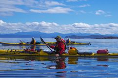 Tres kayakers baten sus barcos en las aguas inmóviles de Hardy Bay fotografía de archivo