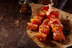 Tres kebabs de los pescados crudos en la tabla con aceite Imagenes de archivo
