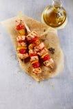 Tres kebabs de los pescados en la tabla con la botella de aceite Fotografía de archivo libre de regalías