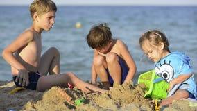 Tres Kisd que juega en orilla de mar metrajes