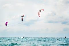Tres kitesurfers que disfrutan de la resaca Fotos de archivo libres de regalías