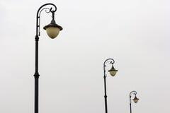 Tres lámparas de calle en fondo del cielo nublado Fotos de archivo