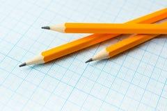 Tres lápices amarillos en el papel para los dibujos en el cuadrado imágenes de archivo libres de regalías