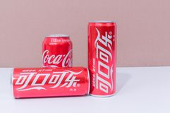 Tres latas de Coca-Cola con dos escritos en chino foto de archivo