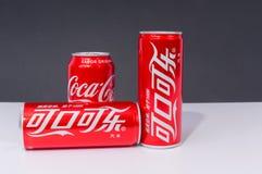 Tres latas de Coca-Cola con dos escritos en chino imagen de archivo libre de regalías