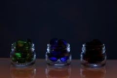 Tres latas de las píldoras, píldoras coloridas en los bancos, vidrio Fotografía de archivo