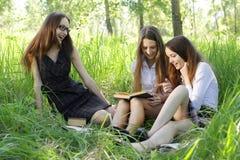 Tres libros de lectura de los estudiantes al aire libre Imagen de archivo