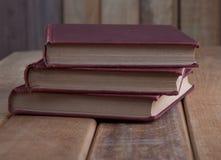 Tres libros del vintage en la tabla de madera rústica Fotografía de archivo