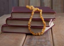 Tres libros del vintage en la tabla de madera rústica con Amber Necklace Foto de archivo libre de regalías