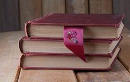 Tres libros del vintage en la tabla de madera rústica con la cinta de la señal Foto de archivo