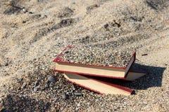 Tres libros rojos en la arena, cubierta con la arena, concepto de transience del tiempo, empañaron el fondo Imágenes de archivo libres de regalías