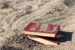Tres libros rojos en la arena, cubierta con la arena, concepto de transience del tiempo, empañaron el fondo Fotos de archivo libres de regalías