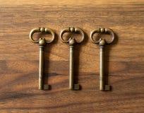 Tres llaves de bronce alineadas en una superficie de madera Foto de archivo