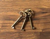 Tres llaves de bronce idénticas que ponen en una superficie de madera Imágenes de archivo libres de regalías