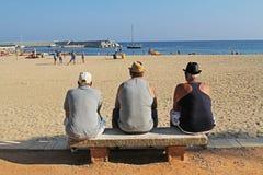 Tres más viejos hombres se sientan en un banco y la mirada del mar en la playa de Blanes Fotografía de archivo libre de regalías