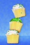 Tres magdalenas de la vainilla clavadas con tachuelas encima de uno a Foto de archivo libre de regalías