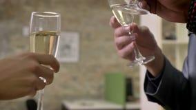 Tres manos de los trabajadores del negocio tintinean los vidrios con champán en la oficina, concepto del partido de la compañía almacen de video