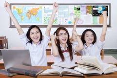 Tres manos emocionadas del aumento de las colegialas en la clase Foto de archivo libre de regalías