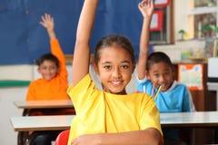 Tres manos primarias de los alumnos levantaron en clas Fotos de archivo