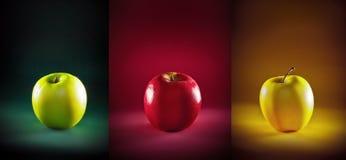 Tres manzanas coloreadas en diverso fondo Foto de archivo libre de regalías