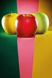 Tres manzanas coloreadas en diverso fondo Fotografía de archivo libre de regalías