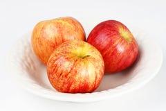 Tres manzanas en el tazón de fuente blanco Fotos de archivo libres de regalías
