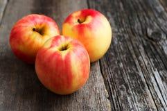 Tres manzanas en fondo de madera Imagen de archivo