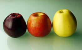 Tres manzanas en fondo verde Imágenes de archivo libres de regalías