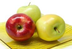 Tres manzanas en una placa Foto de archivo libre de regalías