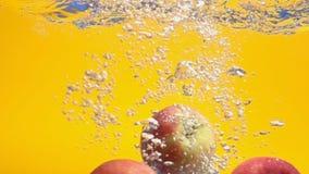 Tres manzanas rojas en la cámara lenta que baja en el agua almacen de metraje de vídeo