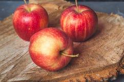 Tres manzanas rojas en una sierra de madera foto de archivo