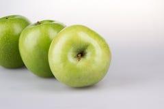 Tres manzanas verdes en el fondo blanco Imágenes de archivo libres de regalías