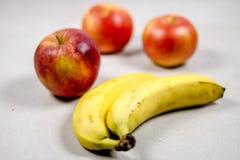 Tres manzanas y dos plátanos aislaron la composición en el fondo blanco fotografía de archivo libre de regalías