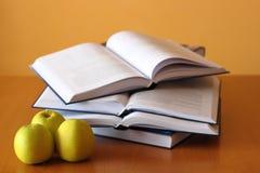 Tres manzanas y libros verdes Imagenes de archivo