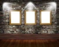 Tres marcos del oro en la pared de ladrillo Fotografía de archivo