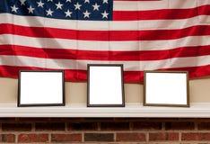 Tres marcos en blanco de la foto en un estante con el fondo de la bandera americana Imágenes de archivo libres de regalías