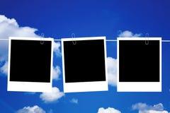 Tres marcos en blanco de la foto que cuelgan en línea Fotografía de archivo