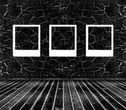 Tres marcos en la pared agrietada negra Foto de archivo