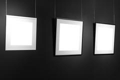 Tres marcos vacíos en la pared negra Carteles del espacio en blanco o marco del arte que espera para ser llenado Marcos blancos y Foto de archivo