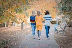 Tres mejores amigos atractivos alegres de las mujeres jovenes que caminan y que se divierten junto afuera foto de archivo