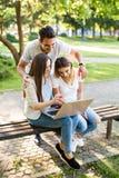 Tres mejores amigos en parque que disfrutan del día y que usan el ordenador portátil para Fotos de archivo libres de regalías