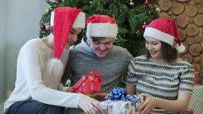 Tres mejores amigos que se divierten, llevando a cabo presentes y sentándose cerca del árbol de navidad Primer almacen de metraje de vídeo