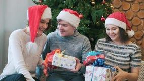 Tres mejores amigos que se divierten, llevando a cabo presentes y sentándose cerca del árbol de navidad Primer almacen de video