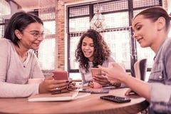 Tres mejores amigos que sienten que sorprenden mientras que muestra las fotos después de viajar junto foto de archivo