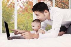Tres meses de bebé que usa el ordenador portátil con el papá Imágenes de archivo libres de regalías