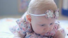 Tres meses del bebé con los ojos azules Niño recién nacido, pequeña muchacha pacífica y atenta adorable mirando la sonrisa sorpre almacen de video