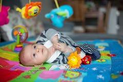 Tres meses felices del bebé, jugando en casa en una a colorida Foto de archivo libre de regalías