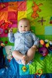 Tres meses felices del bebé, jugando en casa en una a colorida Imagenes de archivo