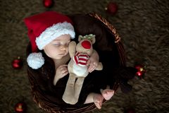 Tres meses lindos del bebé con el sombrero del oso en una cesta, durmiendo Fotografía de archivo