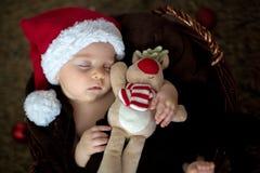 Tres meses lindos del bebé con el sombrero del oso en una cesta, durmiendo Foto de archivo libre de regalías